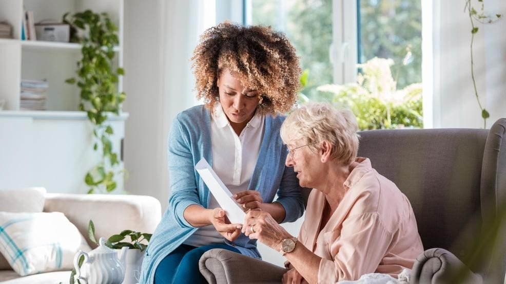 senior reading with caregiver