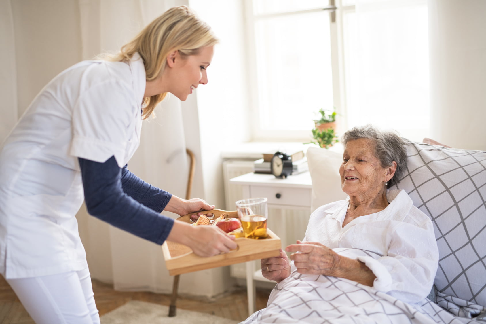 senior being handed food by senior care taker