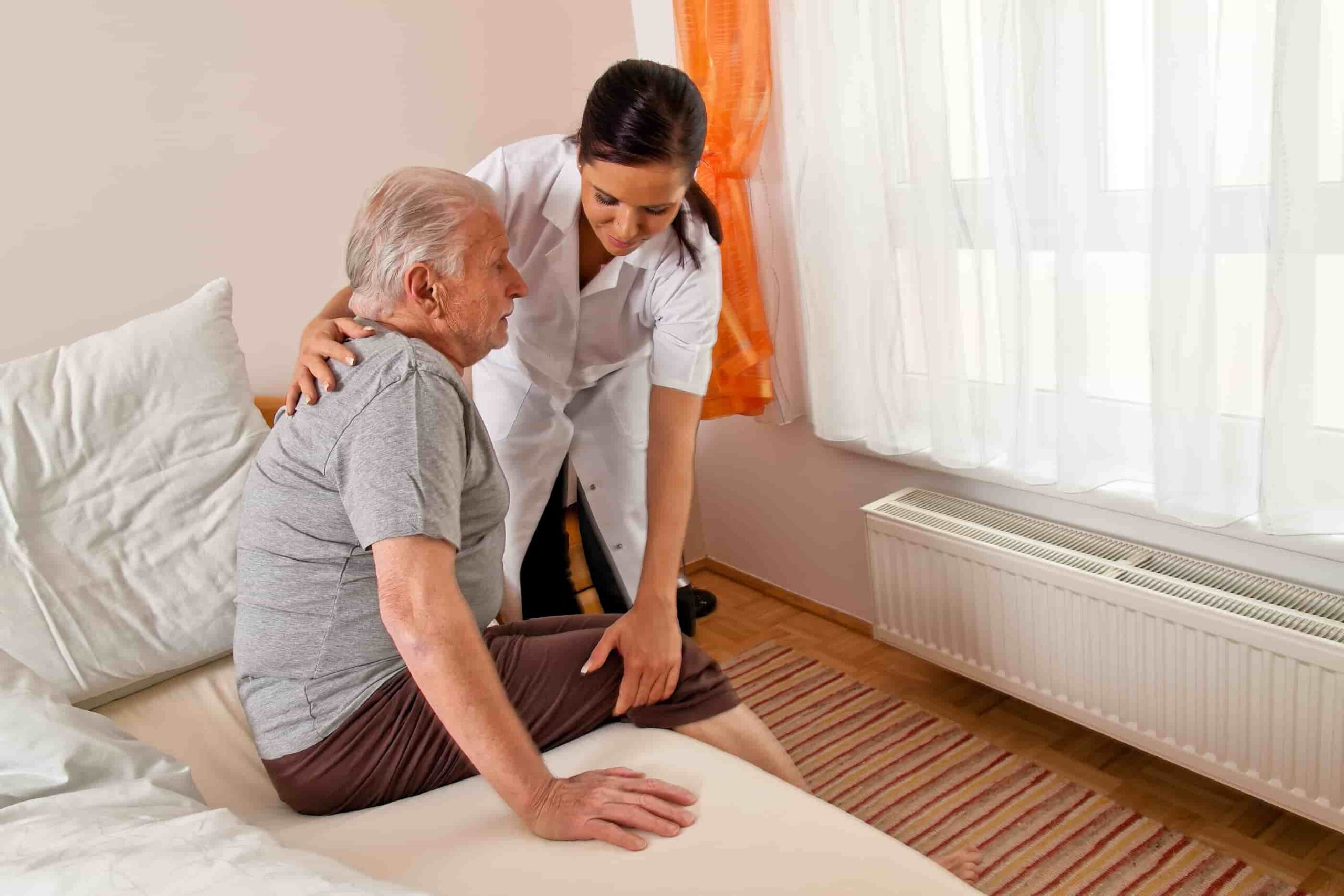 Nursing helping elderly man out of bed